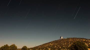 Image of the McDonald Observatory sitting faraway on a shrub covered hill overlooking surrounding grasslands