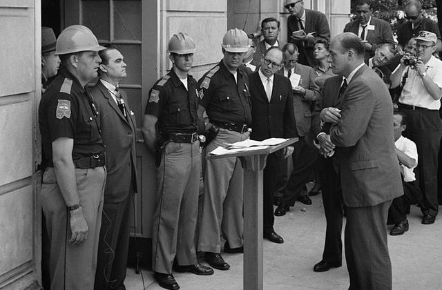 Attempting to block integration at the University of Alabama, Governor George Wallace stands defiantly at the door while being confronted by Deputy U.S. Attorney General Nicholas Katzenbach. 11 June 1963. Via Wikipedia.