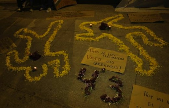Cempasuchil petals form human-shaped outlines on the ground beside lit candles and a placard during an event held in remembrances of the 43 missing student teachers from the Ayotzinapa. Via REUTERS/Henry Romero