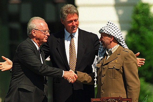 Israeli Prime Minister Yitzhak Rabin, left, shaking hands with PLO Chairman Yasser Arafat, with U.S. President Bill Clinton in the center at the Oslo Accords signing ceremony, Sept. 13, 1993. (Vince Musi / The White House)