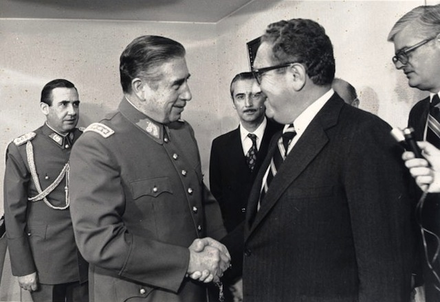 Chilean dictator Augusto Pinochet shaking hands with Kissinger in 1976. Via Wikipedia.