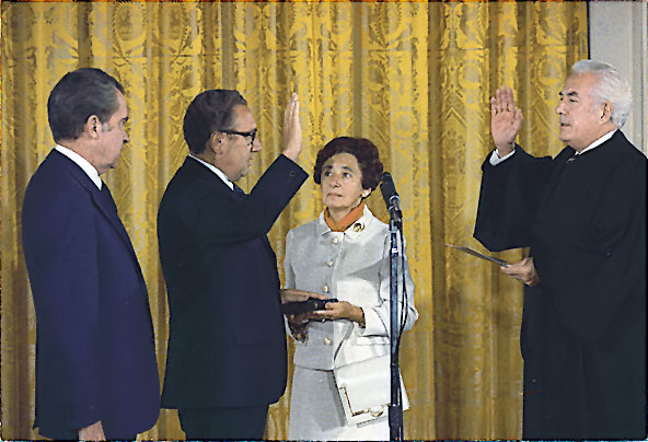 Kissinger being sworn in as Secretary of State by Chief Justice Warren Burger, September 22, 1973. Kissinger's mother, Paula, holds the Bible upon which he was sworn in while President Nixon looks on. Via Wikipedia.