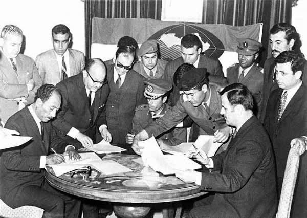 Syria´s President Hafez al-Asad (sitting on the right side) signing the Federation of Arab Republics in Benghazi, Libya, on April 18, 1971 with President Anwar al-Sadat (stting left) of Egypt and Colonel Muammar al-Qaddafi of Libya (sitting in the centre). The agreement never materialized into a federal union between the three Arab states. Photo Credit: The Online Museum of Syrian History via Wikimedia Commons.