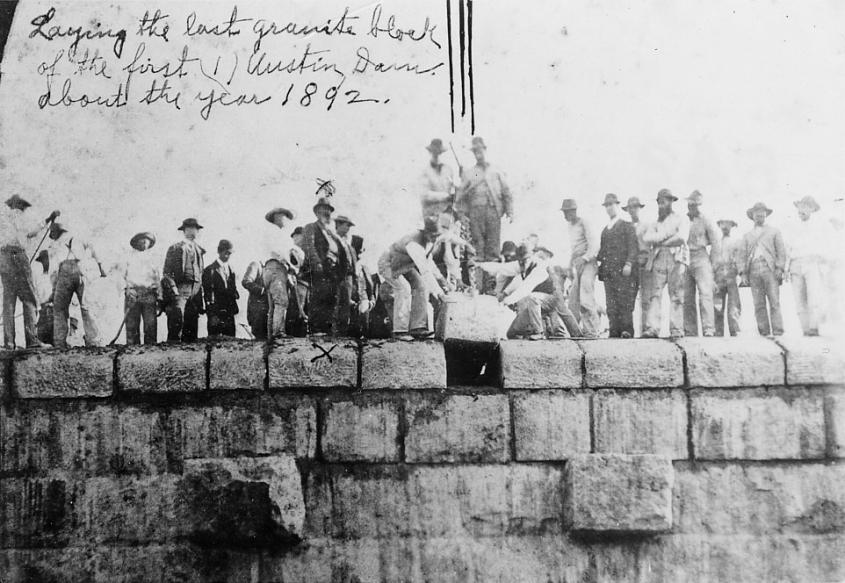 Black and white image of a group of men laying large granite blocks for the first Austin Dam in 1892