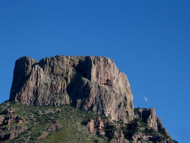 Image of a rocky mountain top against a blue, cloudless sky in Big Bend National Park with the moon visible in background