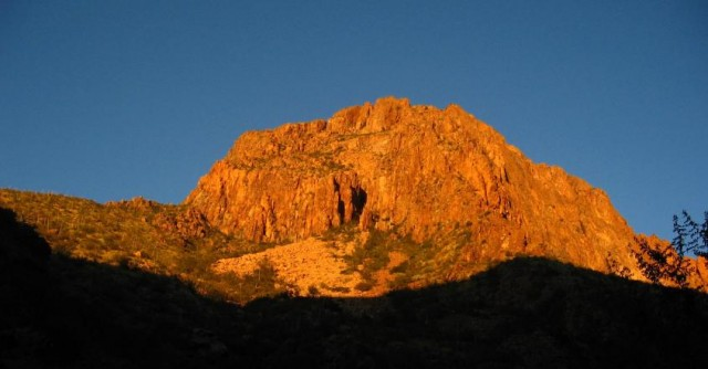 Image of rocky mountain top in full sunlight against a cloudless blue sky