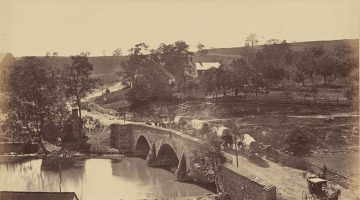Black and white image of covered wagons crossing the stone bridge at Antietam