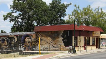 Photograph of the front facade of the Victory Grill showing a mural of African American figures painted along the side of the building