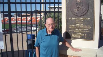 Photograph of Clyde Rabb Littlefield standing next to a plaque memorializing his father