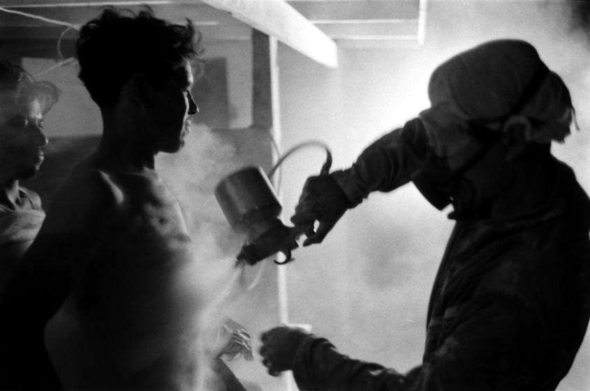 Black and white photograph of a Bracero worker being sprayed with DDT in 1959 with a spray gun