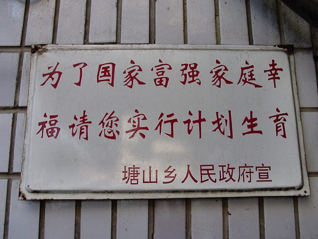 "Government sign in Tangshan Township: ""For a prosperous, powerful nation and a happy family, please practice family planning...Please for the sake of your country, use birth control. Sign put up by the government. Found in the entry to the alley slums in Nanchang. These slums are where the pregnant women hide from the government officials enforcing the one child policy. (Wikimedia Commons)"