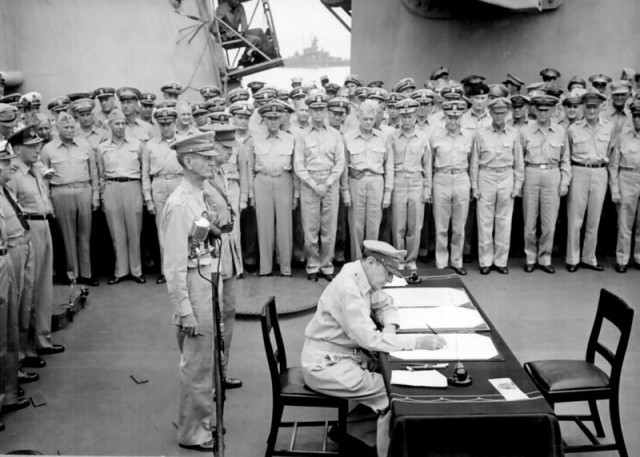MacArthur signs the Japanese surrender document aboard the USS Missouri (National Archives and Records Administration)