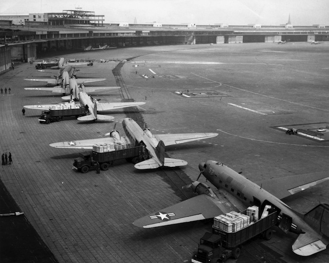 U.S. Navy Douglas R4D and U.S. Air Force C-47 aircraft unload at Tempelhof Airport during the Berlin Airlift. 1948-49