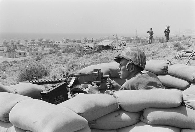 U.S. Marine sits in a foxhole and points a machine gun towards Beirut, Lebanon, in the distance.