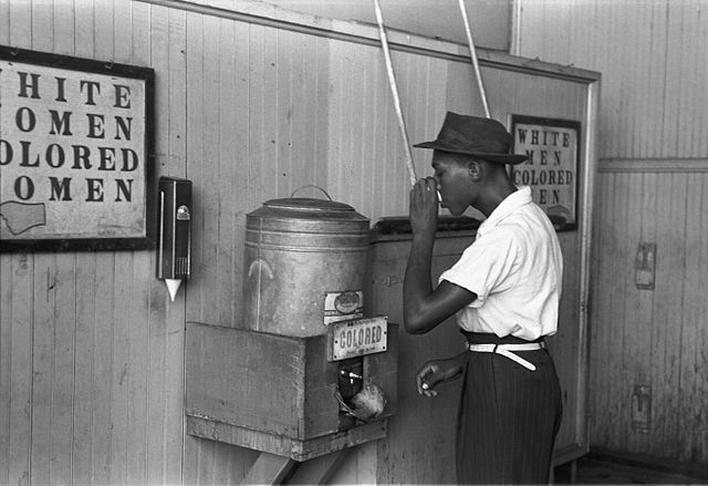 "An African-American man drinking at a ""colored"" drinking fountain in a streetcar terminal in Oklahoma City, 1939. Courtesy of the Library of Congress."