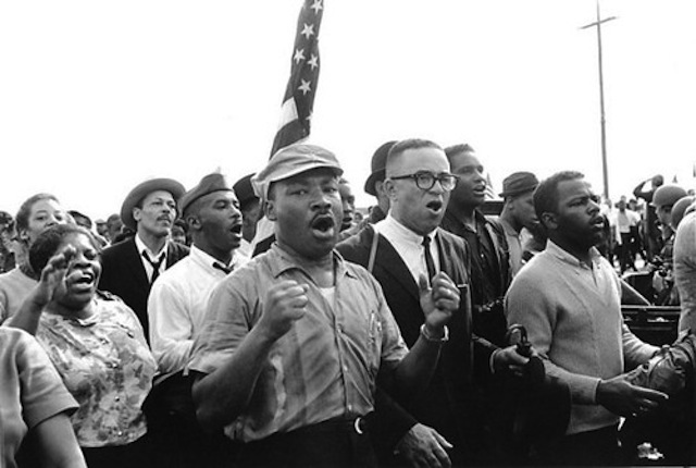 Martin Luther King Jr. and Civil Rights activists singing Freedom songs on the Selma to Montgomery March in 1965. Via Jacobin magazine.