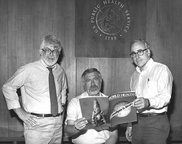 This 1980 photograph taken at the Centers for Disease Control, depicted three former directors of the Global Smallpox Eradication Program as they read the good news that smallpox had been eradicated on a global scale. From left to right, Dr. J. Donald Millar, who was Director from 1966 to 1970; Dr. William H. Foege, who was Director from 1970 to 1973, and Dr. J. Michael Lane, who was Director from 1973 to 1981. Via Wikipedia.