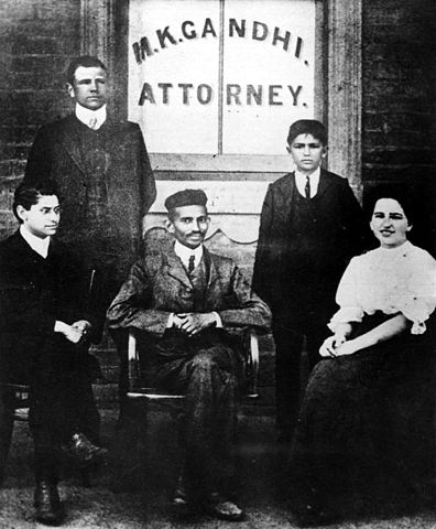 Gandhi (center) with his secretary, Miss Sonia Schlesin, and his colleague Mr. Polak in front of his Law Office, Johannesburg, South Africa, 1905. Via Wikipedia.
