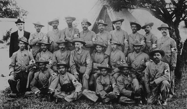 Gandhi with the stretcher-bearers of the Indian Ambulance Corps during the Boer War, South-Africa. Via Wikipedia.