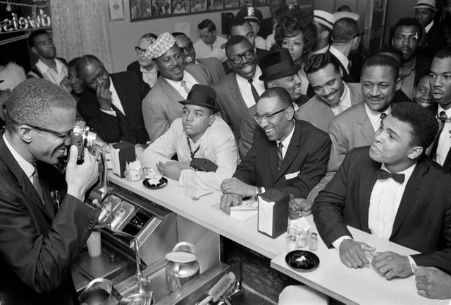 Malcolm X photographs Ali in February 1964, after his first defeat of Sonny Liston to become world heavyweight champion. Via Wikipedia.