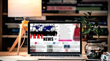 "Stylized picture of a laptop sitting on a nicely decorated desk displaying the words ""fake news"" on a blurred out online article"
