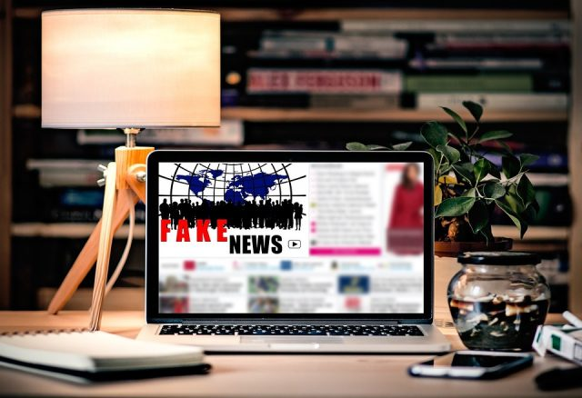"""Stylized picture of a laptop sitting on a nicely decorated desk displaying the words """"fake news"""" on a blurred out online article"""