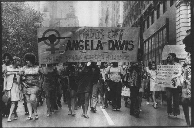"Members of the Third World Women's Alliance in NYC marching in 1972 and carrying a banner that reads ""Hands off Angela Davis"" (Credit: Luis Garza)"