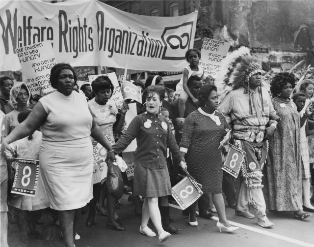 Members of the Third World Women's Alliance marching in NYC in 1972 with a banner reading Welfare Rights Organization (Credit: Luis Garza).
