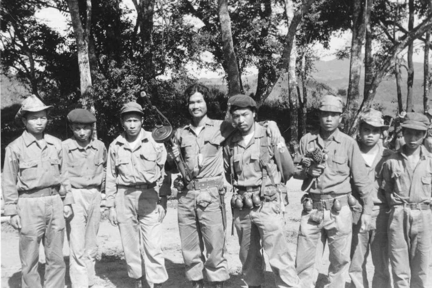 Black and white photograph of eight armed Hmong fighters