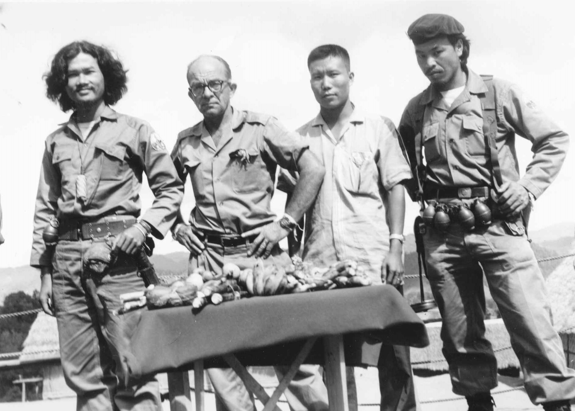 """Black and white image of """"Pop"""" Buell with three Hmong fighters"""