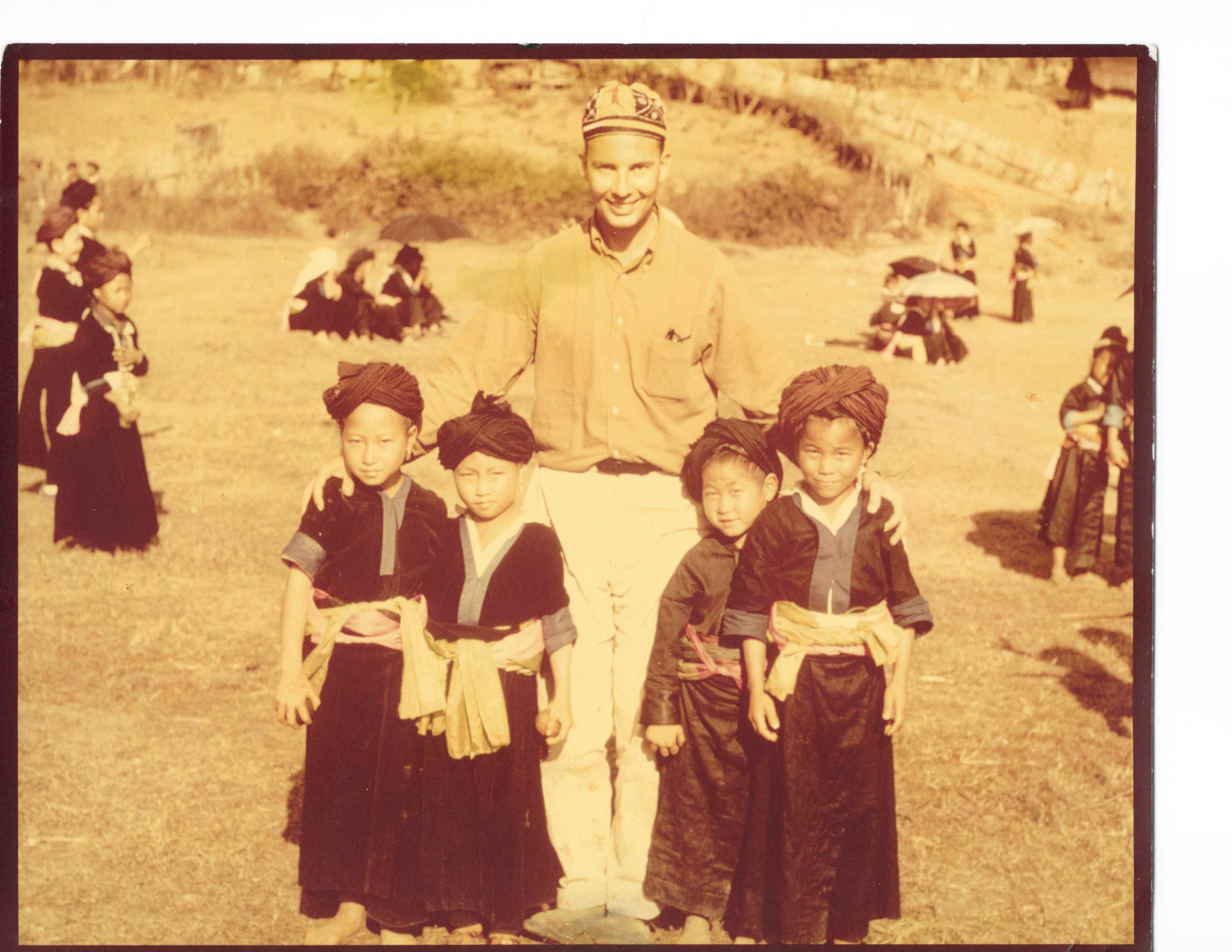 Black and white photograph of Tom Ward with Hmong children in Sam Thong, Laos in 1965