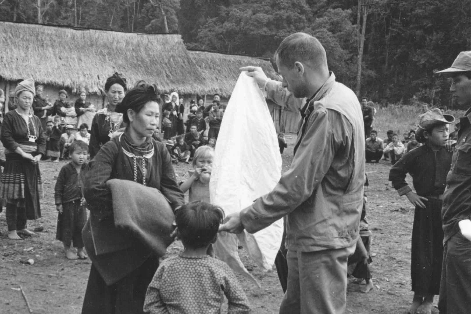 Black and white photograph of Americans distributing relief supplies to Hmong villagers