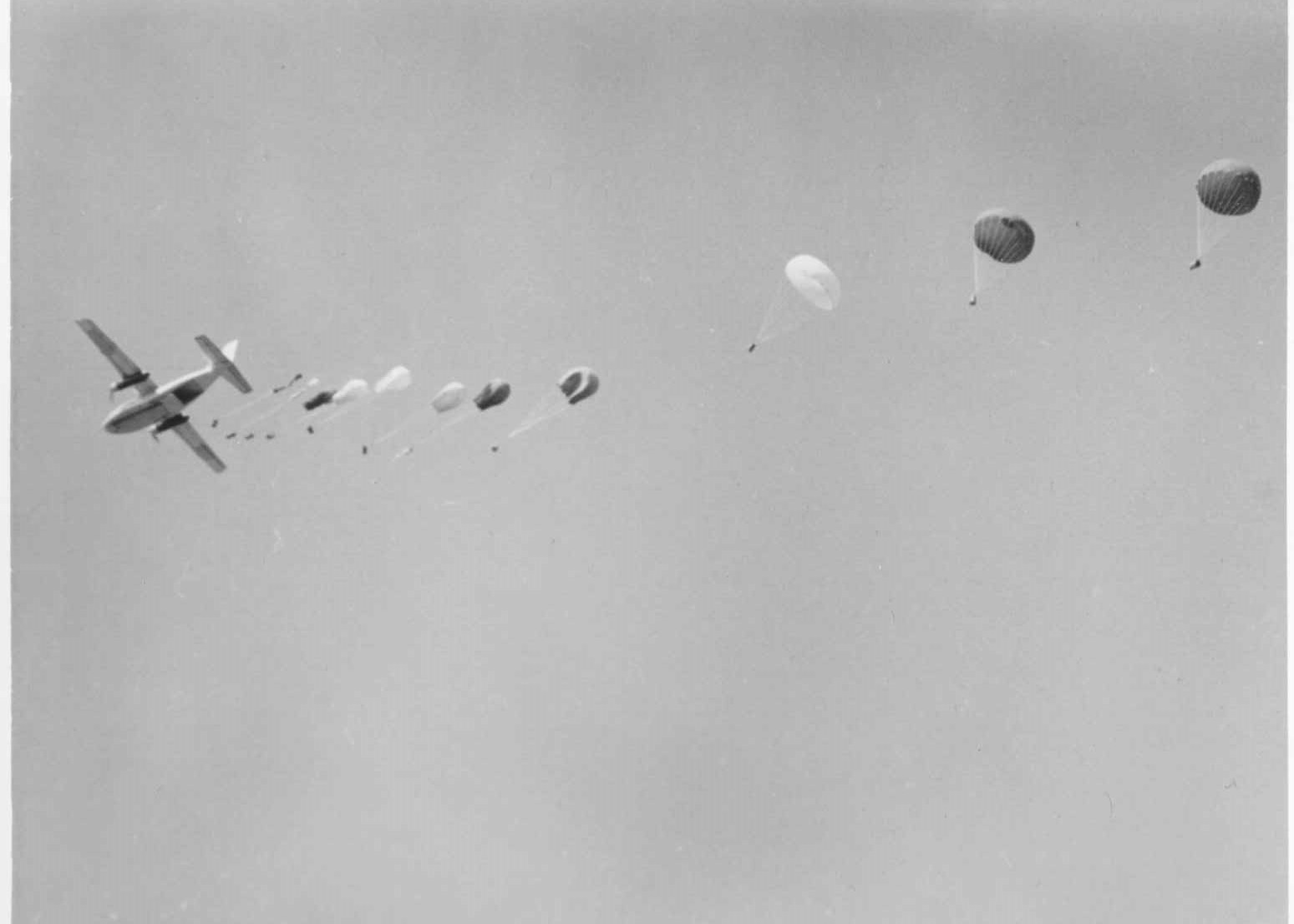 Black and white photograph of a twin-engine airplane dropping supplies via parachute during flight