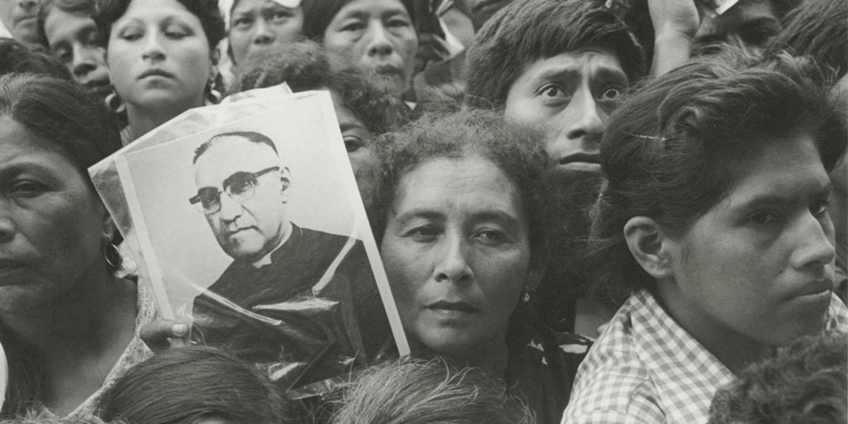 A woman carries a photo of Romero as she walks through a crowd of mourners