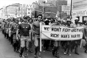 """Veterans protest and carry a sign that reads """"We won't fight another rich man's war"""""""