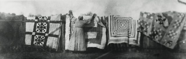 An African American woman is hanging quilts on a clothes line.