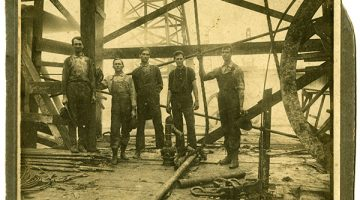 Black and white image of five men standing underneath an oil rig