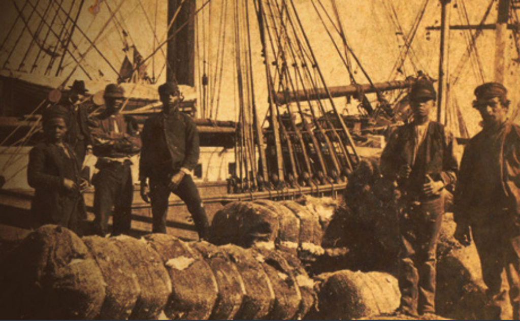 Shipworkers in Savannah, Georgia. On the left, one Black woman and two Black men look toward the photographer with a white man behind them. On the right, a young Black man stands beside a white man.