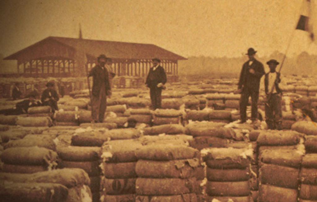 Dock workers in Savannah, Georgia stand on tall mounds of packaged goods.