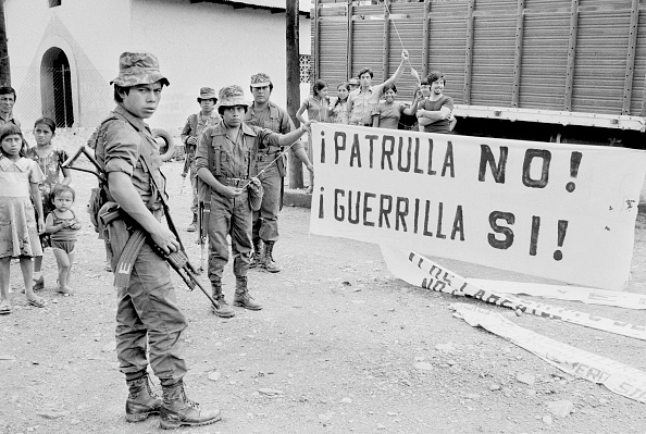 Residents of Huehuetenango watch as Guatemalan army soldiers show captured banners made by a militant guerrilla group. Banner reads: Patrulla No! Guerrilla Si!