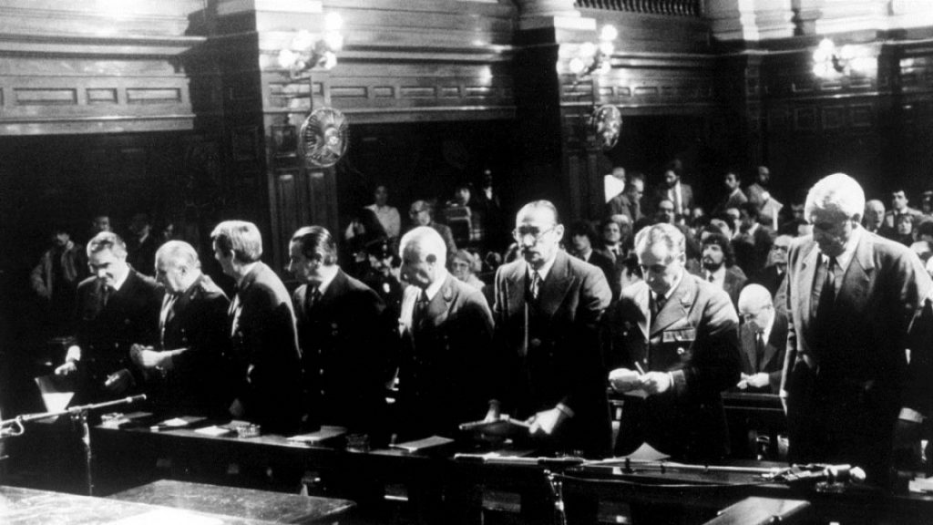 The military commanders in the courtroom. One general looks at the camera.