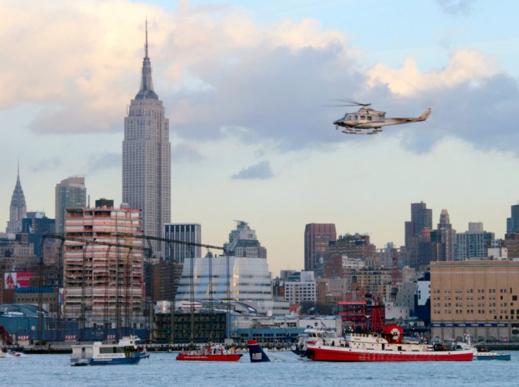 Helicopter hovers over the Hudson River as emergency services respond to a crashed flight.