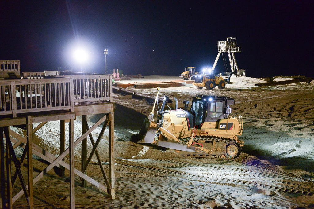 Excavators and construction vehicles perform beach nourishment during nighttime