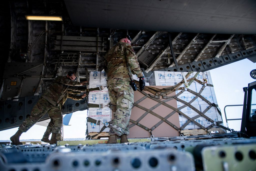U.S. Air Force Airmen assist with coordinating and unloading more than 150,000 pounds of bottled water brought in via aircraft
