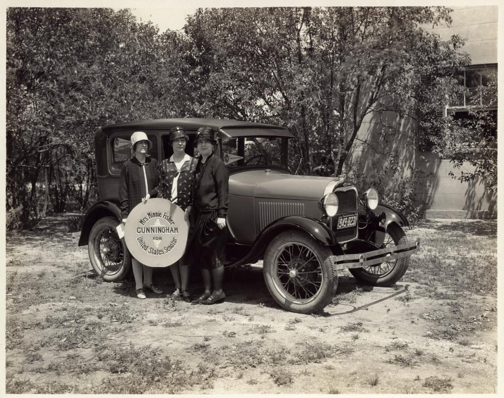 """Minnie Fisher Cunningham (far right) and two other women in front of car holding sign that reads: """"Mrs. Minnie Fisher Cunningham for United States Senator."""" Photo Courtesy of the Austin History Center"""