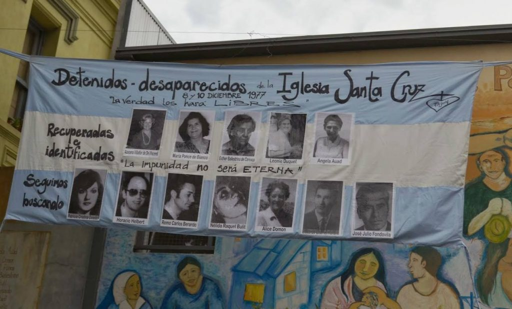 A blue and white banner with victims' photos honors the memory of those disappeared from the Santa Cruz Parish.