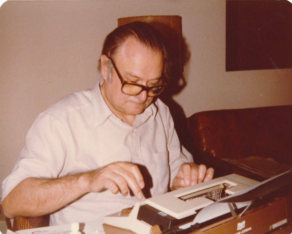 Emilio Mignone sits at a typewriter.