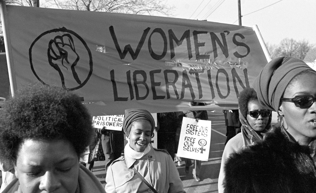 """Four black women march beneath a sign reading """"women's liberation"""". In the background, a smaller sign reads: """"Free our sisters, free ourselves."""""""