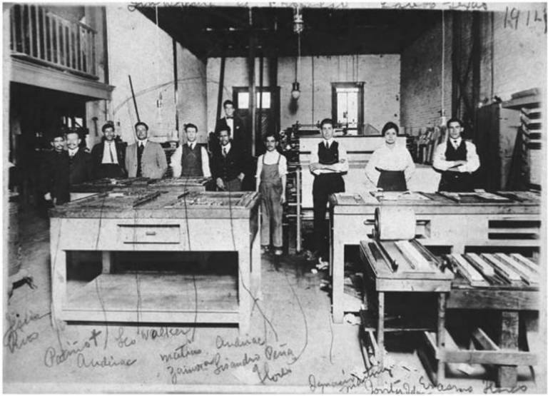 A group of men and one women stand facing the camera in a print shop