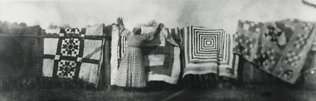A woman hangs quilts on a clothing line.